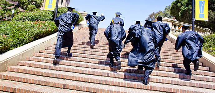 students in graduation gowns running up stairs