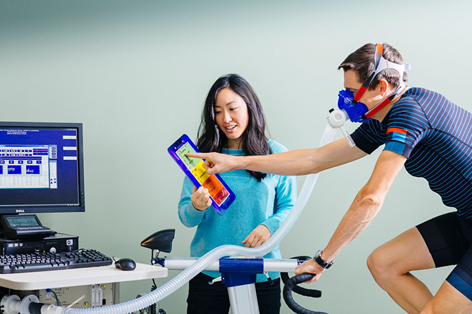 UC San Francisco research fellow Cheri Mah, shown here with cyclist Kurt Wolfgang, studies sleep and performance in elite athletes, and consults with professional sports teams to improve their athletes' sleep habits.